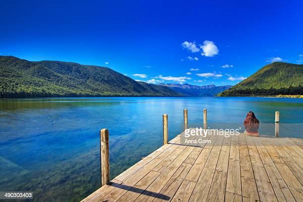 Woman sits on dock at Lake Rotoroa