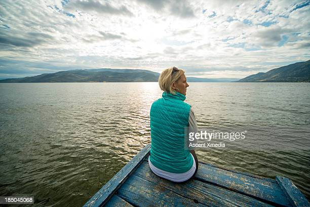 Woman sits on end of lake pier, looks away