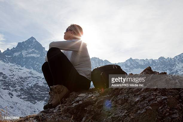 Woman sits on mountain summit, sunrise
