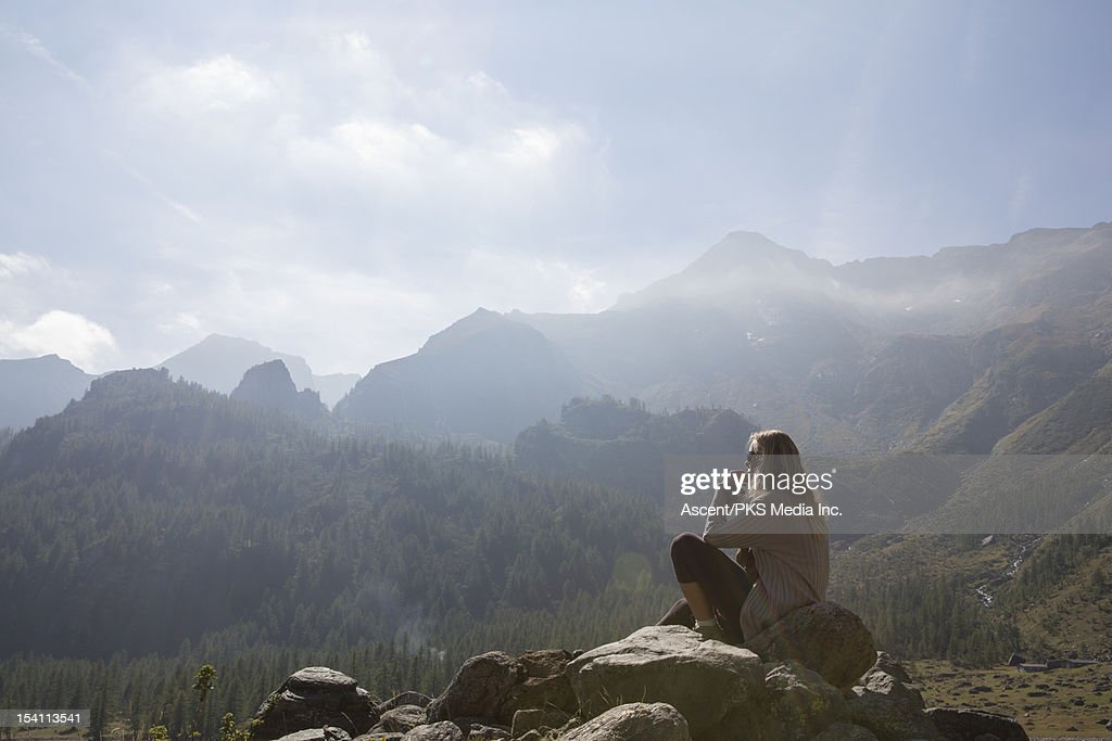 Woman sits on rock in meadow, in mountains : Stock Photo