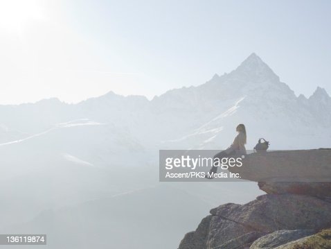 Woman sits on rock ledge above valley, mtns : Stock Photo