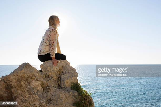 Woman sits on rocky summit above sea, looks out