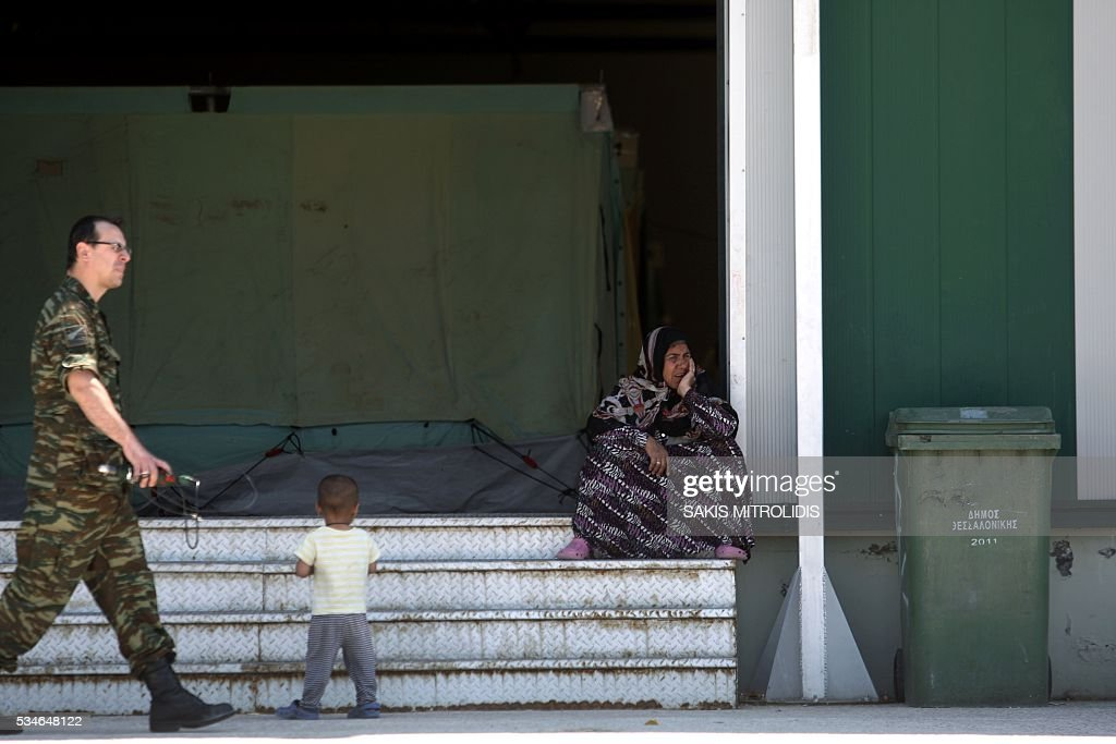 A woman sits on stairs inside a new camp for refugees and migrants set in an abandoned factory in Sindos, a west suburb of Thessaloniki on 27 May, 2016. The squalid Idomeni refugee camp in northern Greece which became a symbol of Europe's migrant crisis has been fully evacuated, police said Thursday, as another 30 died crossing the Mediterranean. In the space of three days, police transferred about 4,000 migrants by bus from Idomeni to newly created camps in the industrial outskirts of Greece's second city Thessaloniki. / AFP / SAKIS