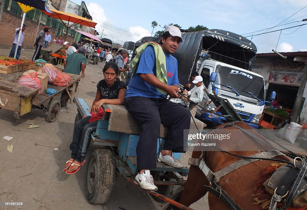 A woman sits on the back of a horse driven wagon in Barrio Bolivar day market on January 23, 2013 in Popayan, Colombia.