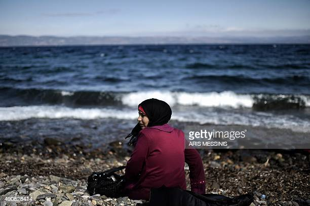 A woman sits on the beach after arriving with other refugees and migrants at the Greek island of Lesbos after crossing the Aegean sea from Turkey on...