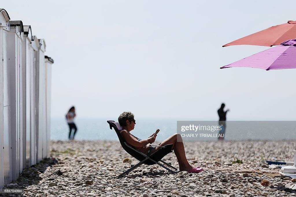 A woman sits on the beach in a deck chair reading on a sunny day in Le Havre, northwestern France, on May 27, 2016. / AFP / CHARLY