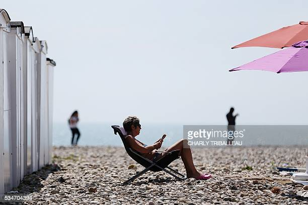 A woman sits on the beach in a deck chair reading on a sunny day in Le Havre northwestern France on May 27 2016 / AFP / CHARLY TRIBALLEAU