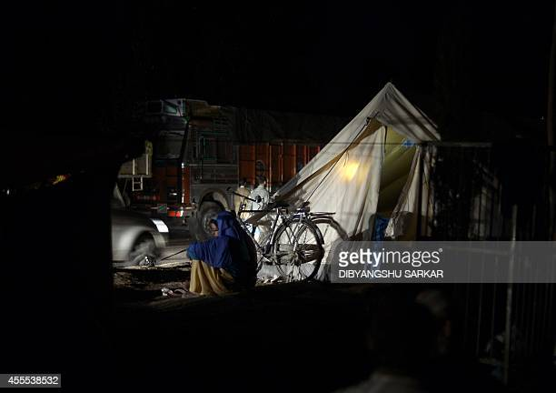 A woman sits on the central isle of a highway where displaced families have setup tents in Srinagar the summer capital of the Indian State of Jammu...