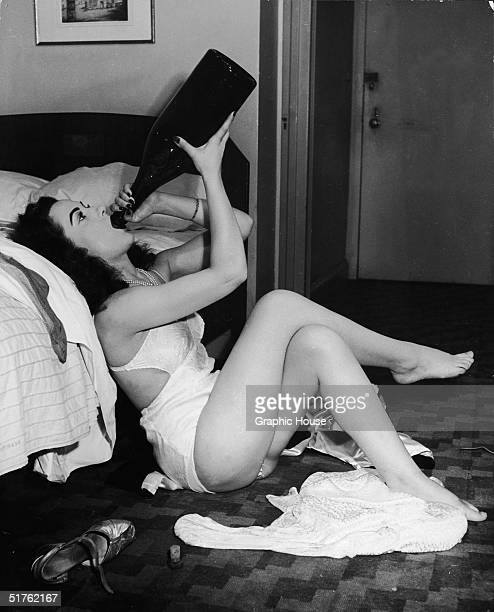 A woman sits on the floor of her hotel room in her underwear leaning against the bed and with a magnum of champagne turned up to her mouth Her...