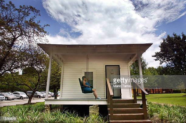 A woman sits on the front porch of the tworoom house where Elvis Presley was born January 8 1935 during Elvis Week August 14 2002 in the singer's...