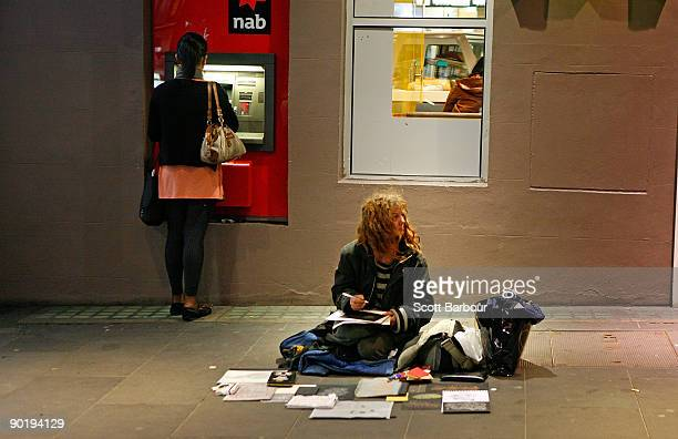 A woman sits on the pavement as a woman behind her withdraws money from an ATM machine during the �Hands Up for the Homeless� campaign on August 31...
