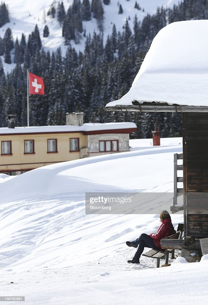 A woman sits outside a mountain hut at the top of the Schatzalp funicular railway in the town of Davos, Switzerland, on Saturday, Jan. 19, 2013. Next week the business elite gather in the Swiss Alps for the 43rd annual meeting of the World Economic Forum in Davos, the five day event runs from Jan. 23-27. Photographer: Chris Ratcliffe/Bloomberg via Getty Images