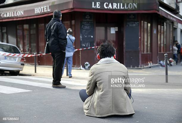 A woman sits outside of the Carillon bar in the 10th district of Paris on November 14 following a series of attacks in and around the city leaving at...