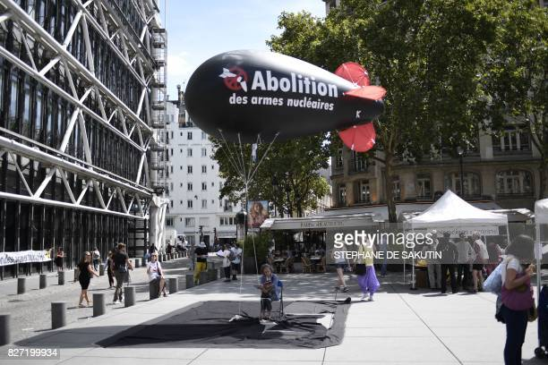 A woman sits underneath a balloon shaped like a nuclear bomb outside the Centre Georges Pompidou in Paris on August 7 during an action and fourday...
