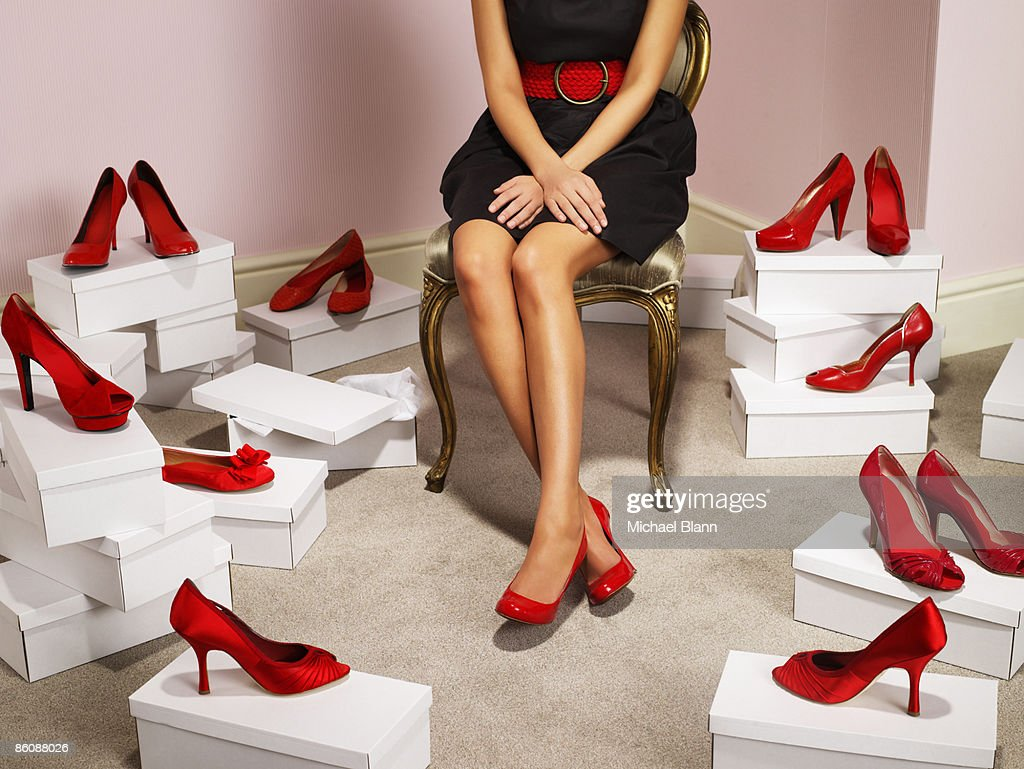 Woman sits wearing red shoes, others surround her : Stock Photo