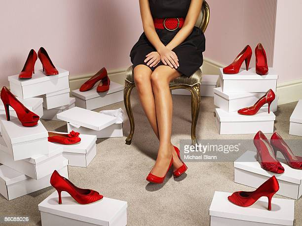 Woman sits wearing red shoes, others surround her