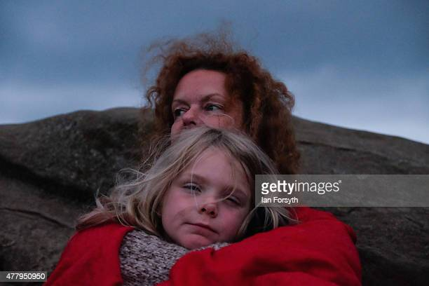 A woman sits with her daughter after spending the night at the ancient stone circle at Castlerigg as they celebrate dawn on the summer solstice on...