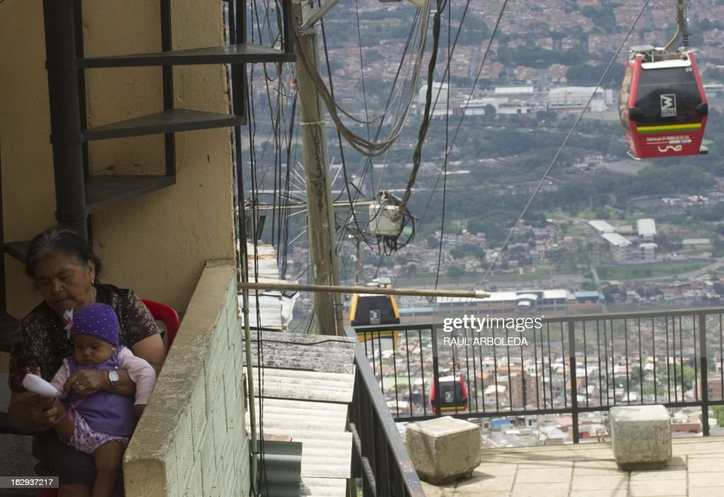 "A woman sits with her granddaughter in their house as the Metrocable is seen behind, in Santo Domingo Savio neighbourhood, in Medellin, Antioquia department, Colombia on March 1, 2013. Medellin, which competed with New York and Tel Aviv, was chosen by popular vote through the internet, as the ""Innovative City of the Year"" during the City of the Year contest, organized by The Wall Street Journal and Citigroup. The distinction was basically made for its modern transportation system, its public library, escalators built in a shantytown and schools that have allowed the integration of society. AFP PHOTO/Raul ARBOLEDA"