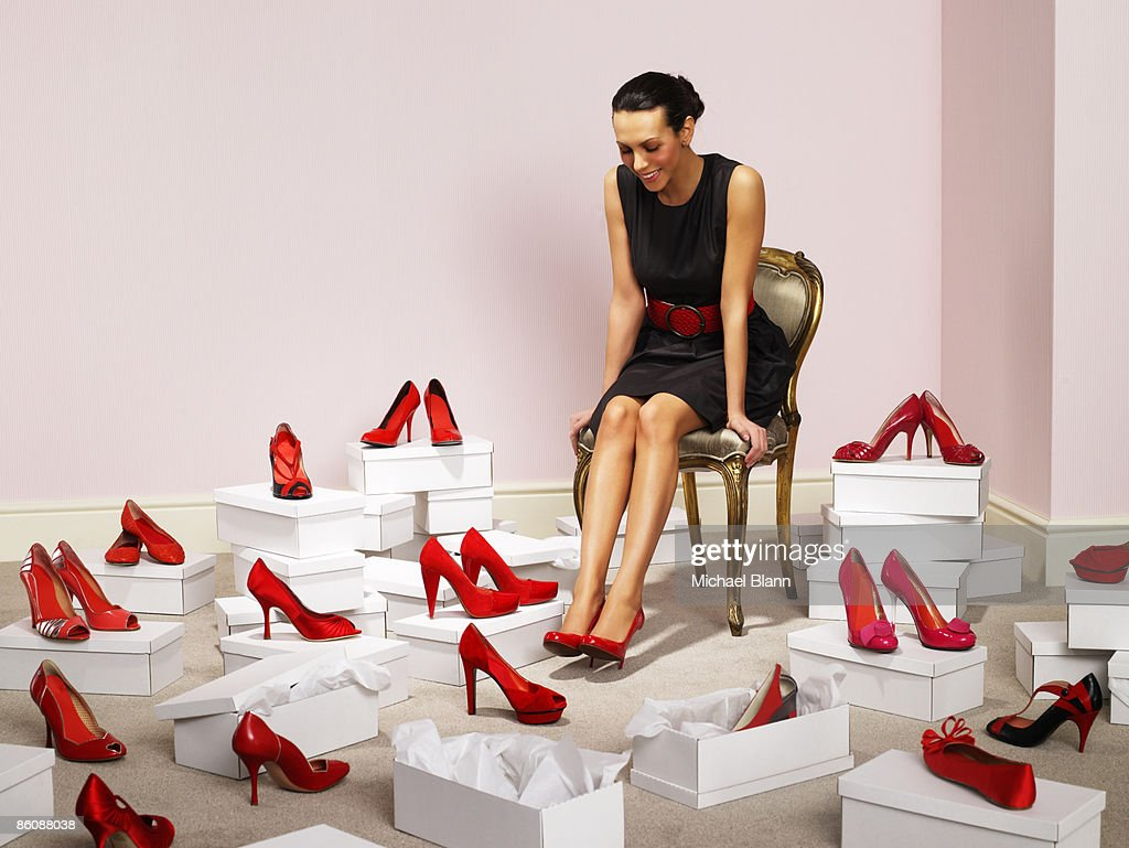 Woman sits with red shoes surrounding her : Foto de stock