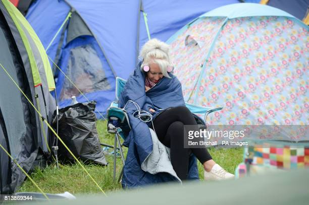 A woman sits wrapped in a sleeping bag amongst tents at Glastonbury Festival Worthy Farm Somerset PRESS ASSOCIATION Photo Picture date Sunday June...