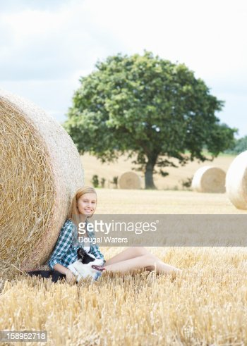 Woman sitting against hay bail in field with dog. : Stock Photo