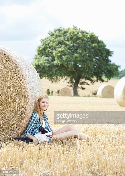 Woman sitting against hay bail in field with dog.