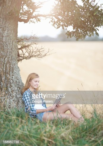 Woman sitting against Oak tree using tablet. : Stock Photo
