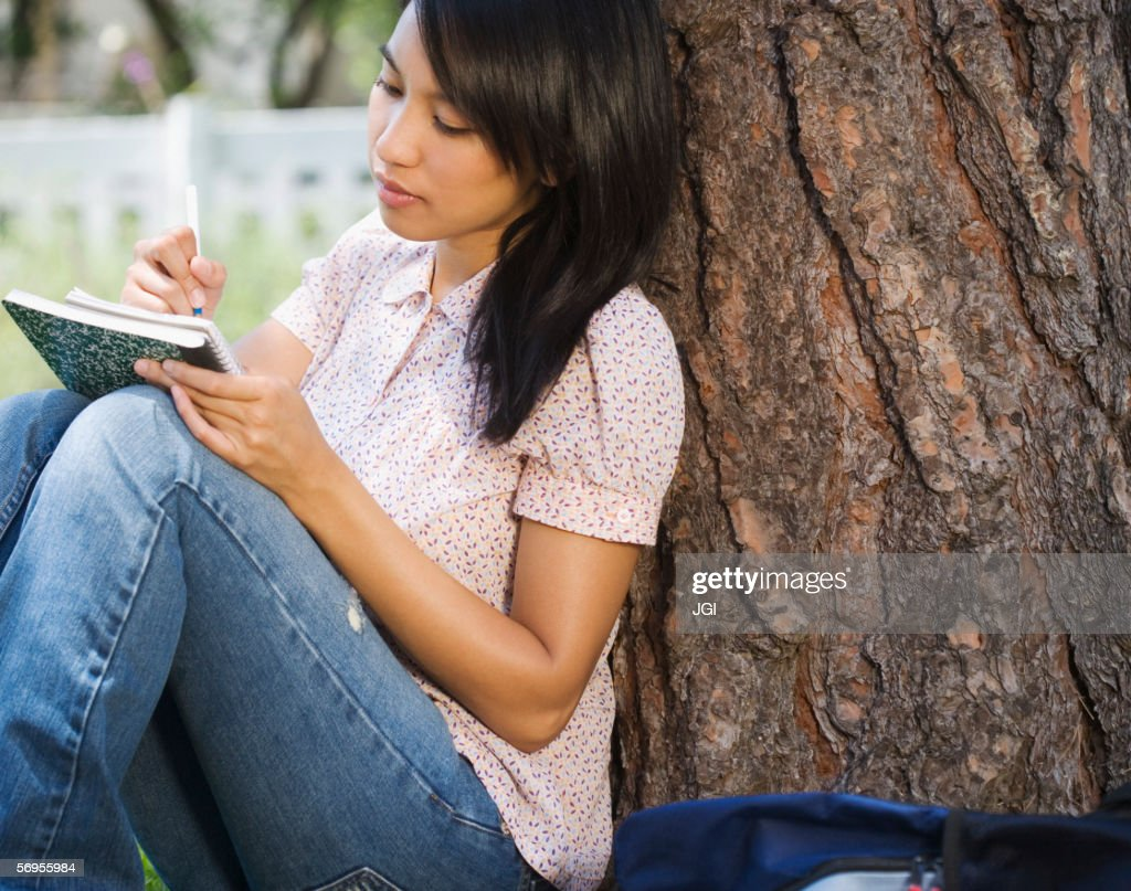 Woman sitting against tree writing in notebook : Stock Photo