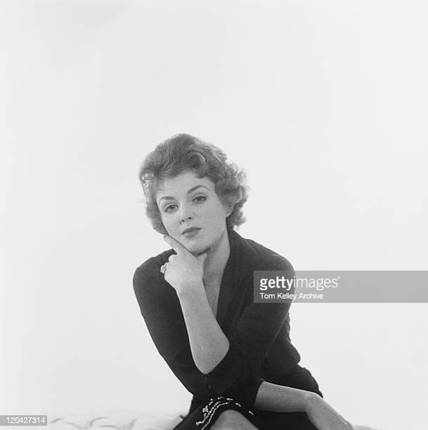 Woman sitting against white background, portrait