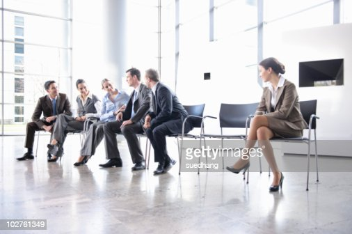 Woman sitting alone separate from group : Stock Photo
