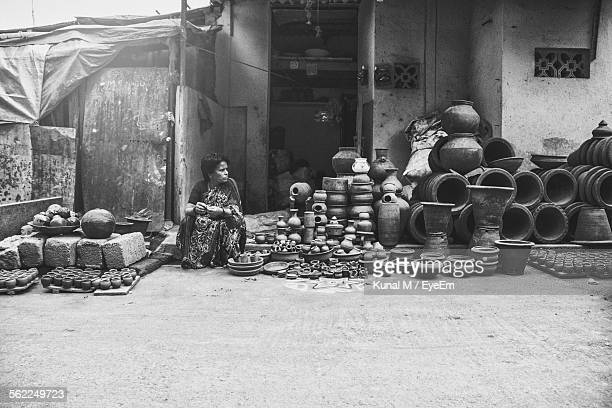 Woman Sitting Amidst Pots Outside Building