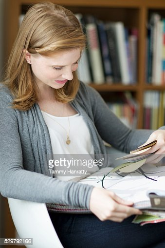 Woman sitting and looking at samples : Bildbanksbilder