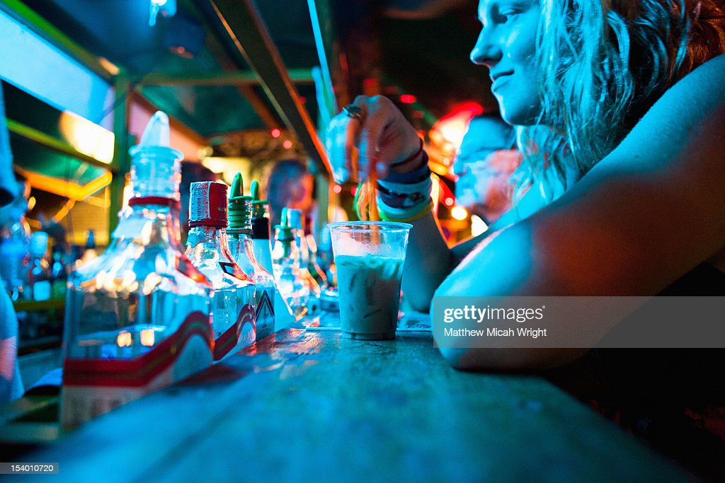 A woman sitting at a bar. : Stock Photo