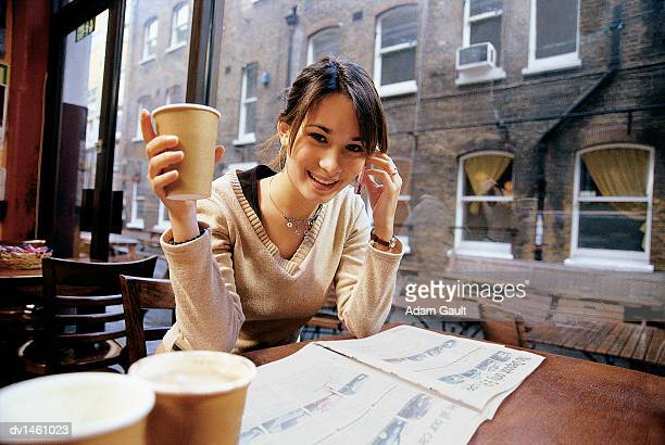 Woman Sitting at a Cafe Table Holding a Cup of Coffee and a Mobile Phone