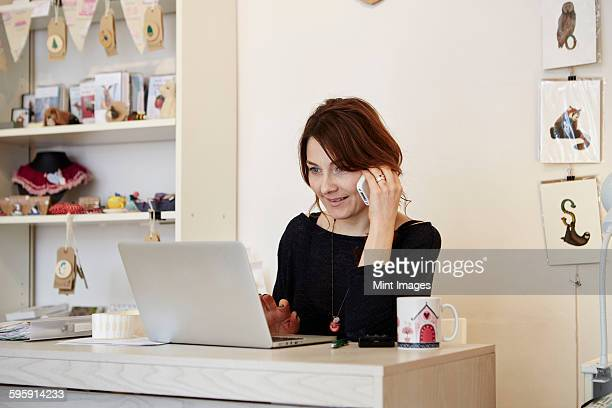 A woman sitting at a desk in a gift shop using a laptop and making a call.