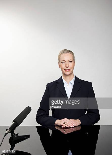 A woman sitting at a desk with a microphone