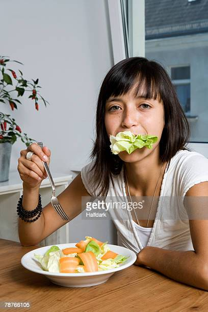 A woman sitting at a table and eating a salad