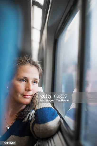 Une femme assise sur un fauteuil près de la fenêtre en train Transport