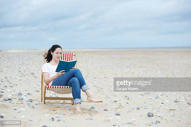 Woman  sitting at beach reading book.
