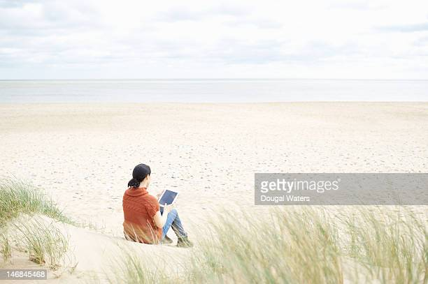 Woman sitting at beach with digital tablet.