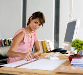 Woman sitting at desk and drawing with ruler