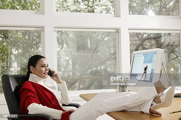 Woman sitting at desk with feet up