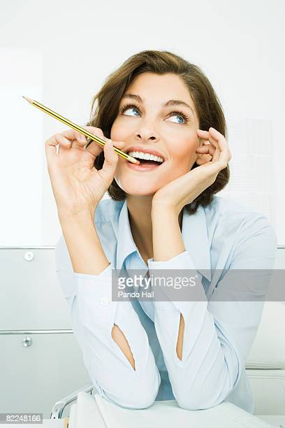 Woman sitting at desk with pencil in mouth