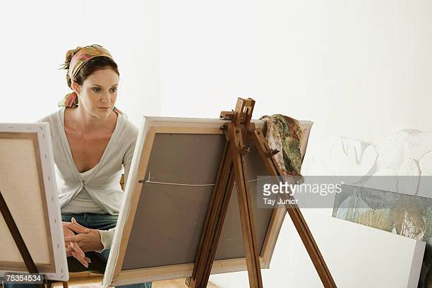 Woman sitting at easel in studio