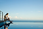 Woman sitting at edge of infinity pool, looking at view
