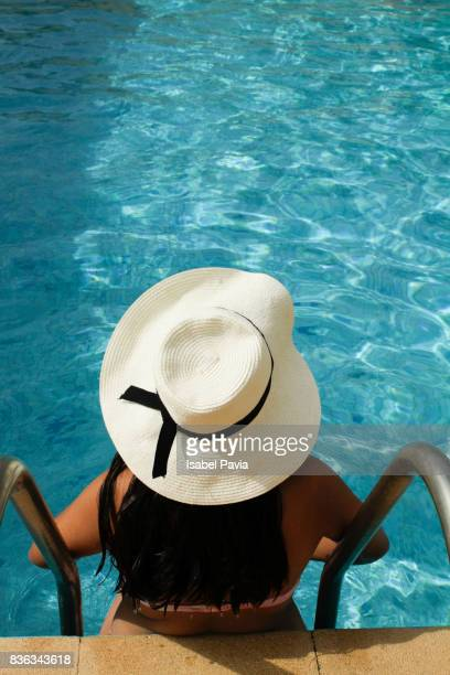 Woman sitting at edge of pool decking