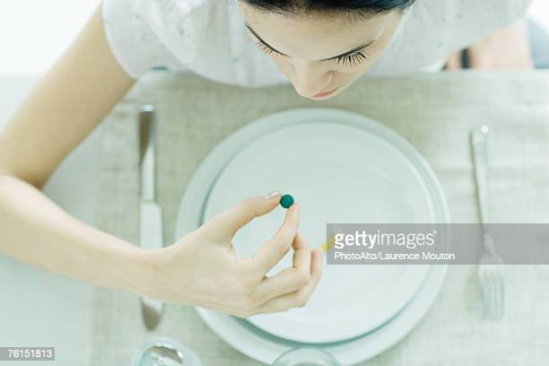 Woman sitting at empty plate holding vitamin