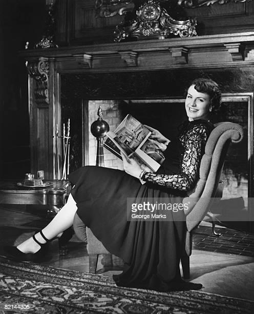 Woman sitting at fireplace, holding magazine, (B&W), portrait