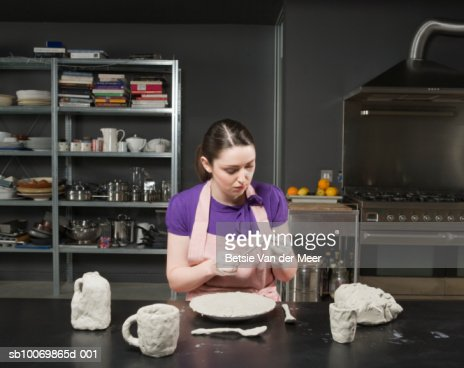 Woman sitting at kitchen table, claying household utilities : Stock Photo