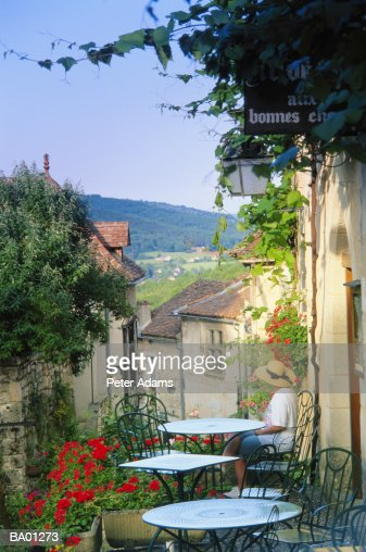 Woman sitting at outdoor cafe overlooking village, elevated view : Foto de stock